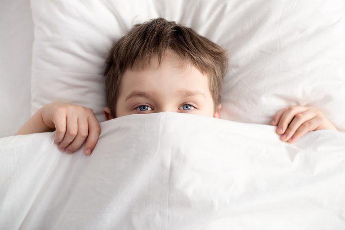 Top view of little boy in bed covering his face with white blanket or coverlet. Sleeping boy. Sleeping child