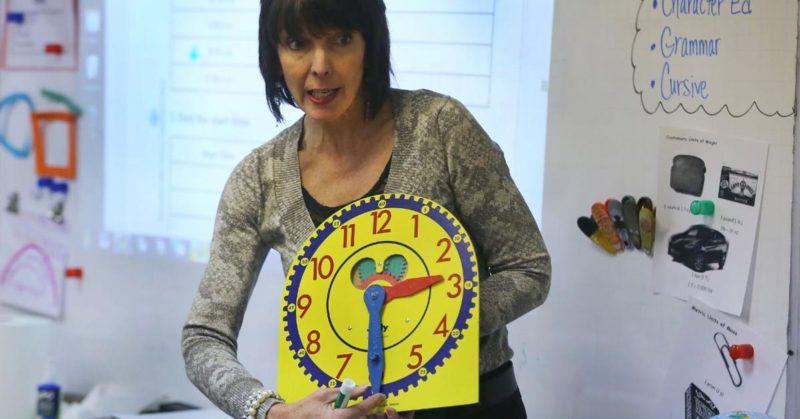school teacher with analog clock